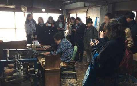 箸作り工場見学を行う大学生